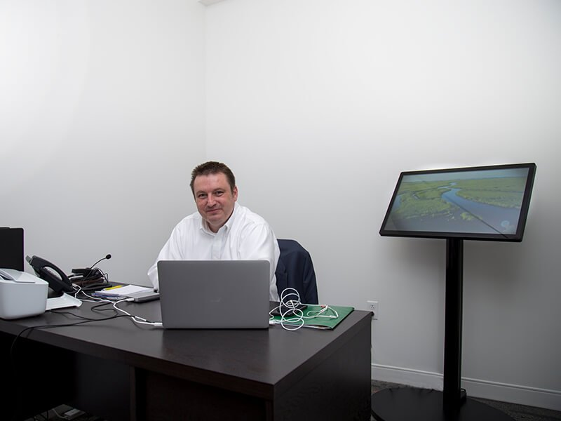 IO staff working on his desk with a computer